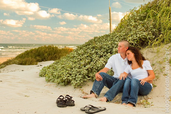 Couple sitting in the dunes waiting for the sun to set during a beach engagement session on Padre Island