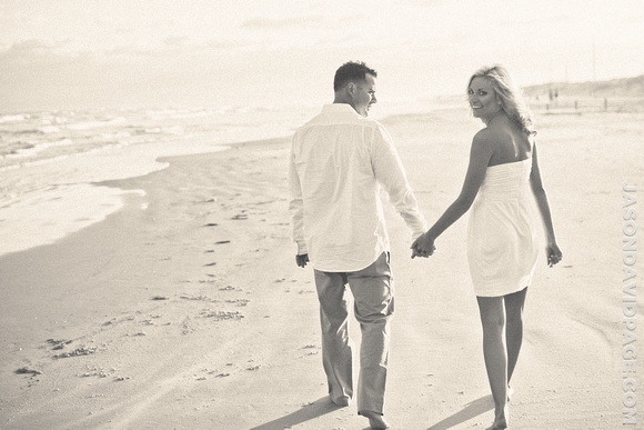 Couple walking down beach during engagement session