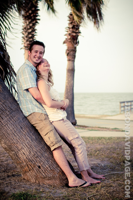 Couple leaning against palm tree at Cole Park during Corpus Christi engagement session