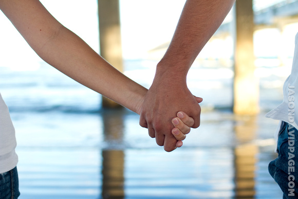 Couple holding hands during beach engagement session on Padre Island