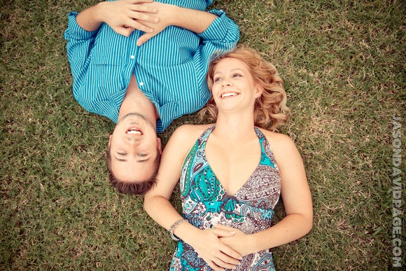 Couple laying on grass in the Watergardens during Corpus Christi engagement session